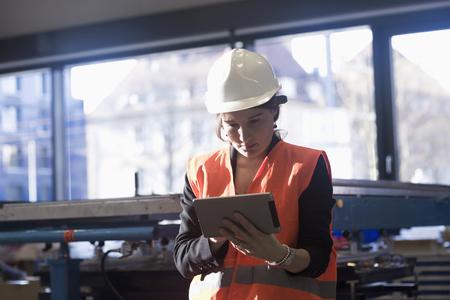 freiburg: Female engineer using a digital tablet in an industrial plant, Freiburg Im Breisgau, Baden-Württemberg, Germany