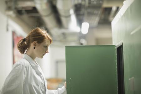 topografo: Young female engineer controlling a switch gear in control room, Freiburg im Breisgau, Baden-Württemberg, Germany