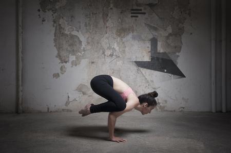 weathered: Mid adult woman practicing bakasana in yoga studio, Munich, Bavaria, Germany