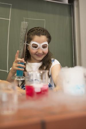 Schoolgirl mixing liquid in chemistry class, Fürstenfeldbruck, Bavaria, Germany
