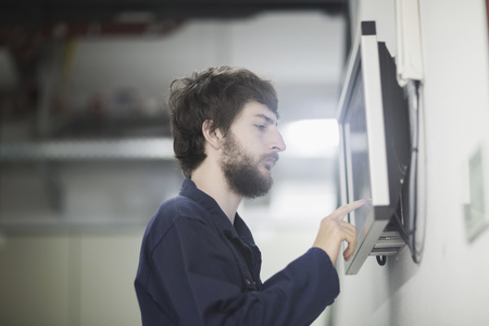 freiburg: Young male engineer working on touchscreen computer monitor in an industrial plant, Freiburg im Breisgau, Baden-Württemberg, Germany LANG_EVOIMAGES