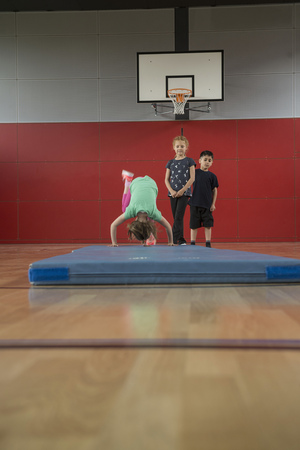 turn about: Girl doing somersault on exercise mat in sports hall with her friends, Munich, Bavaria, Germany