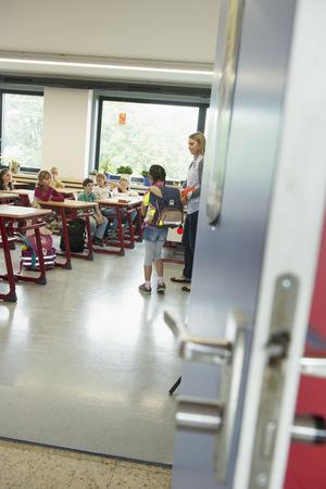 german ethnicity: Female teacher introducing a new classmate in classroom, Munich, Bavaria, Germany