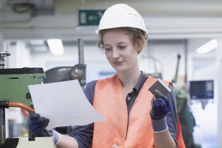 Young female engineer holding machine part with paper in an industrial plant, Freiburg im Breisgau, Baden-Württemberg, Germany