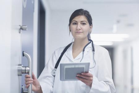 freiburg: Portrait of a young female doctor using digital tablet in hospital corridor, Freiburg im Breisgau, Baden-Württemberg, Germany