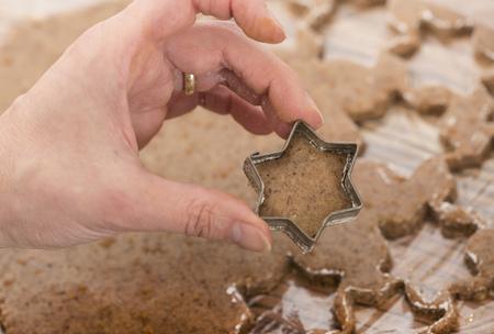 cutter: Close-up of a woman cutting star shape cinnamon, Munich, Bavaria, Germany