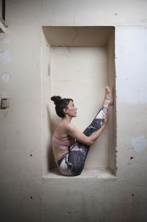 big toe: Mid adult woman practicing big toe pose in alcove, Munich, Bavaria, Germany LANG_EVOIMAGES