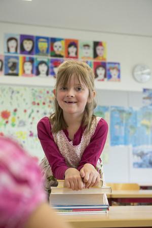 Portrait of a schoolgirl leaning on books, Munich, Bavaria, Germany