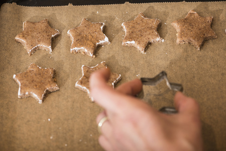 still lifes: Close-up of a woman placing star shape cinnamon on baking sheet, Munich, Bavaria, Germany