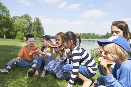 german ethnicity: Children enjoying slices of watermelon at picnic, Munich, Bavaria, Germany