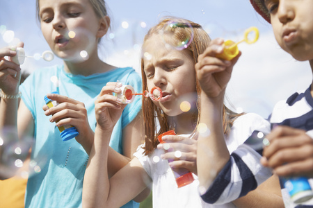 about age: Girls blowing bubbles with bubble wands, Bavaria, Germany LANG_EVOIMAGES