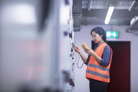 german ethnicity: Young female engineer examining control panel with multimeter in an industrial plant, Freiburg im Breisgau, Baden-Württemberg, Germany LANG_EVOIMAGES