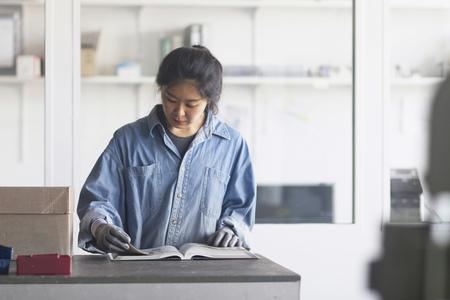 german ethnicity: Young female engineer reading book in an industrial plant, Freiburg im Breisgau, Baden-Württemberg, Germany