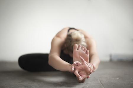 janu: Mid adult woman practicing janu sirsasana pose in yoga studio, Munich, Bavaria, Germany LANG_EVOIMAGES