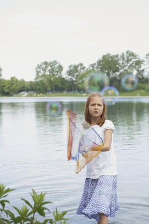 Girl catching soap bubbles with fishing net in the lake, Bavaria, Germany LANG_EVOIMAGES