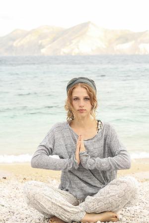 looking away from camera: Healthy woman doing meditation on the beach, Baska, Croatia