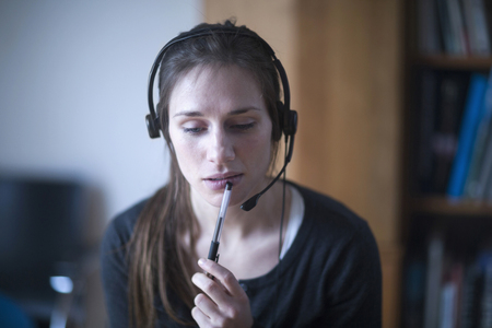 handsfree telephone: Young woman wearing headset and thinking, Freiburg im Breisgau, Baden-Württemberg, Germany