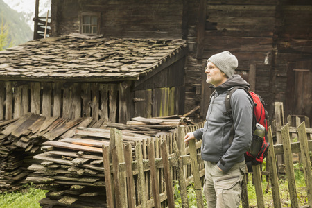 weathered: Mature hiker standing near cottage at rainy day, Austrian alps, Carinthia, Austria