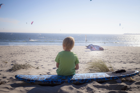 bodyboarding: Rear view of a little child looking at view and sitting on the beach, Viana do Castelo, Norte Region, Portugal