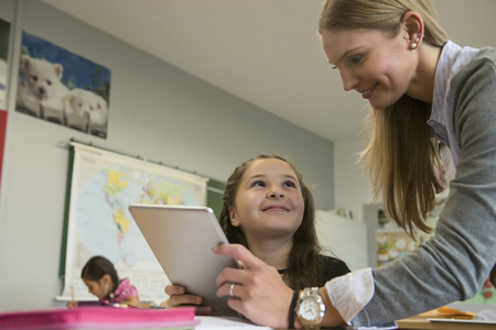 study group: Female teacher showing a girl something on digital tablet pc in classroom, Munich, Bavaria, Germany