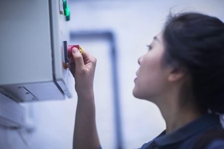 german ethnicity: Young female engineer operating a switch gear in control room, Freiburg im Breisgau, Baden-Württemberg, Germany