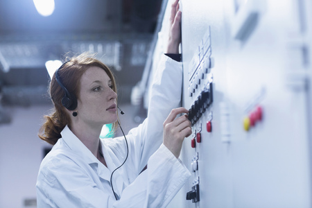 Young female engineer wearing headset and controlling a switch gear in control room, Freiburg im Breisgau, Baden-Württemberg, Germany LANG_EVOIMAGES