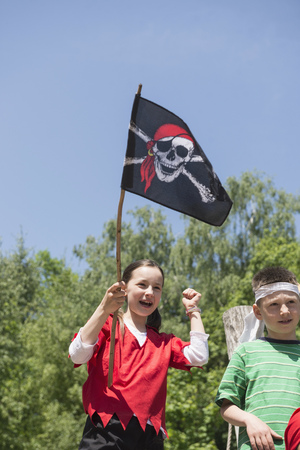 Girl holding pirate flag with her friend in adventure playground, Bavaria, Germany