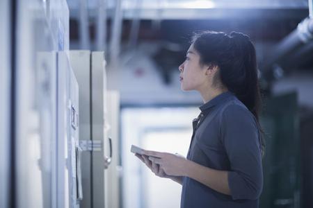 german ethnicity: Young female engineer updating control panel using digital tablet in an industrial plant, Freiburg im Breisgau, Baden-Württemberg, Germany