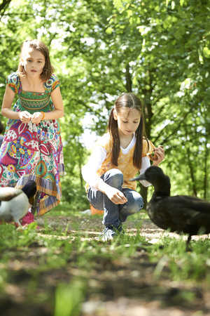 Two girls feeding pretzel to ducks in park, Munich, Bavaria, Germany LANG_EVOIMAGES