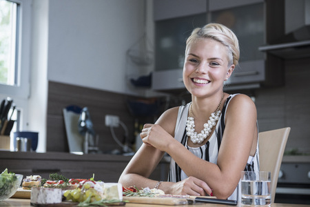 work from home: Portrait of a young woman sitting at kitchen table and smiling, Bavaria, Germany