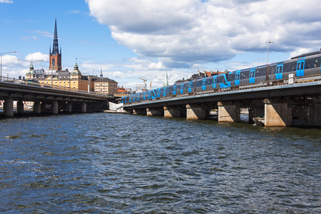 Train on railway bridge in city, Gamla Stan, Stockholm, Sweden LANG_EVOIMAGES