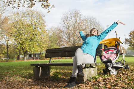 knee boots: Mother stretching while sitting on bench in park by stroller