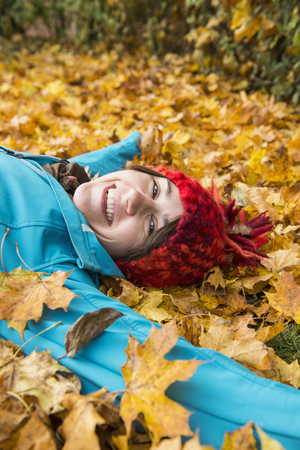 Smiling woman lying on the ground in heap of autumn leaves