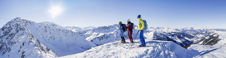 Three skiers standing on snowcapped mountain LANG_EVOIMAGES