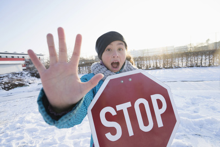 Portrait of girl holding stop sign on snow field LANG_EVOIMAGES