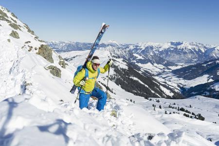 Skier climbing up on ridge of snow mountain