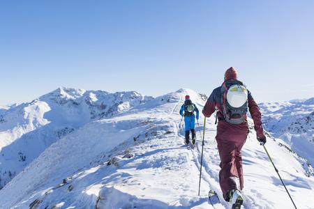 ski walking: Rear view of skiers walking on ridge of mountain against sky