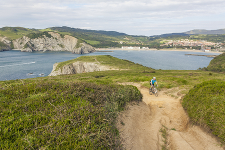 basque country: Mountain biker riding uphill by the sea