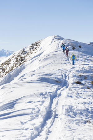 Rear view of skiers climbing snow mountain