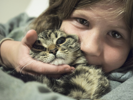 Close-up of girl cuddling with young cat