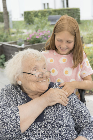 Senior woman on wheelchair with granddaughter at rest home park LANG_EVOIMAGES