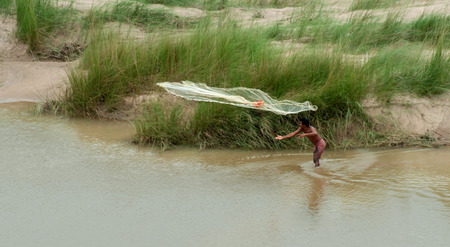 india fisherman: GONGONI, WEST BENGAL   INDIA - OCTOBER 25, 2013  Indian fisherman fishing on Shilaboti river  It is a popular profession at Gongoni village  Editorial
