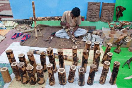 KOLKATA, WEST BENGAL , INDIA - DECEMBER 14TH 2013   Unidentified man making wooden Artworks of handicraft, at Handicraft Fair in Kolkata - the biggest handicrafts fair in Asia