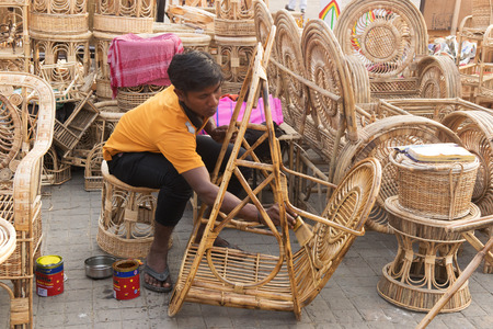 cane chair: Unidentified person polishing Cane furniture handicrafts on display Editorial