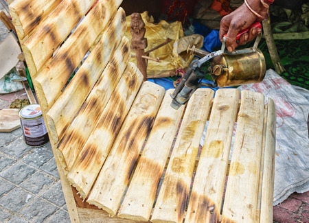 cane chair: KOLKATA, WEST BENGAL , INDIA - NOVEMBER 23RD 2014 : Spraying colour on Cane chair , handicrafts on display during the Handicraft Fair in Kolkata - the biggest handicrafts fair in Asia.