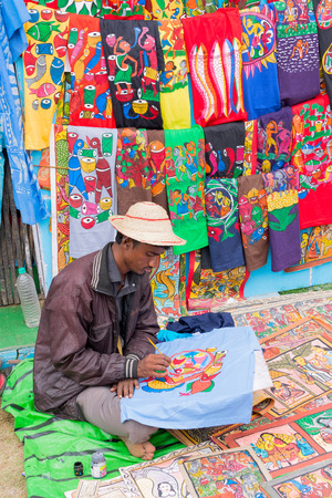 artist painting: KOLKATA, WEST BENGAL , INDIA - DECEMBER 12TH 2014 : Unidentified artist painting handmade clothes, handicrafts show during Handicraft Fair in Kolkata - the biggest handicrafts fair in Asia.