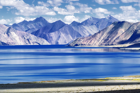 Mountains and Pangong tso (Lake). It is huge lake in Ladakh, altitude 4,350 m (14,270 ft). It is 134 km (83 mi) long and extends from India to Tibet. Leh, Ladakh, Jammu and Kashmir, India Stock Photo