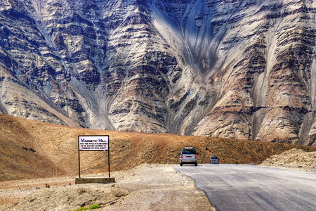A gravity hill where slow speed cars are drawn against gravity is famously known as \Magnetic Hill\ , a natural wonder at Leh, Ladakh, Jammu and Kashmir, India Фото со стока