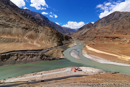 all right: Scenic view of Confluence of Zanskar river from left and Indus rivers from up right - Leh, Ladakh, Jammu and Kashmir, India. This is a famous tourist spot of Ladakh for all seasons.