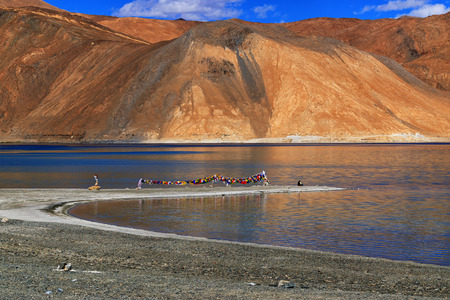 refelction: Refelction of Mountains on Pangong tso (Lake). It is huge lake in Ladakh, altitude 4,350 m (14,270 ft). It is 134 km (83 mi) long and extends from India to Tibet. Leh, Ladakh, Jammu and Kashmir, India Editorial
